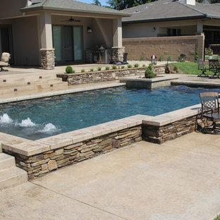 Ejemplo de piscina con fuente elevada, actual, de tamaño medio, rectangular, en patio trasero, con losas de hormigón