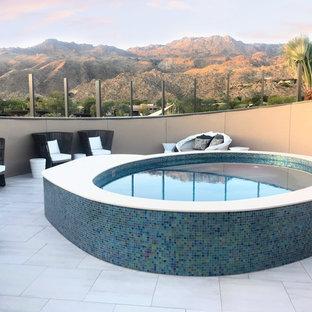 Ejemplo de piscinas y jacuzzis elevados, contemporáneos, redondeados, en azotea, con suelo de baldosas
