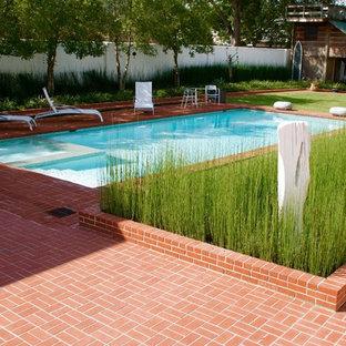 Modelo de piscinas y jacuzzis alargados, minimalistas, grandes, rectangulares, en patio trasero, con adoquines de ladrillo