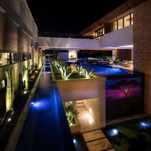 Ejemplo de piscina infinita, contemporánea, extra grande, a medida, en patio, con losas de hormigón