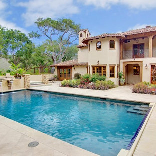 Ispirazione per una grande piscina monocorsia mediterranea rettangolare in cortile con fontane e pavimentazioni in pietra naturale