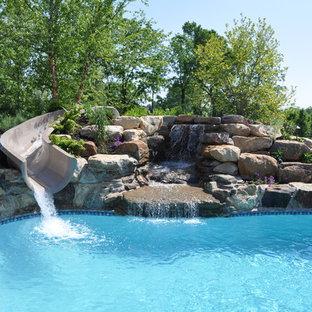 Ejemplo de piscina con tobogán clásica, grande, a medida, en patio trasero, con suelo de baldosas