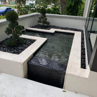 Modelo de piscina con fuente vintage, de tamaño medio, en forma de L, en patio delantero, con adoquines de piedra natural