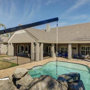 Diseño de piscina con fuente natural, de estilo americano, grande, a medida, en patio trasero, con adoquines de hormigón