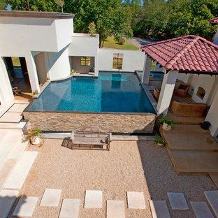 Immagine di una piscina a sfioro infinito mediterranea in cortile con ghiaia