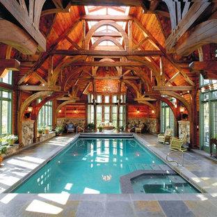 Idee per un'ampia piscina coperta naturale rustica rettangolare con una vasca idromassaggio e cemento stampato