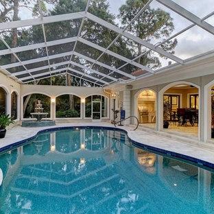 Foto de piscina con fuente alargada, tradicional, grande, interior y a medida, con adoquines de piedra natural