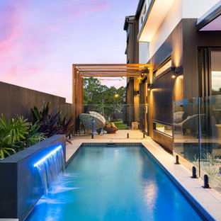 Contemporary rectangular pool in Brisbane with a water feature.