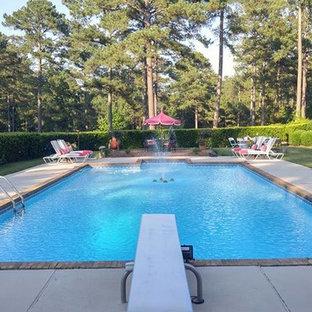 Diseño de piscina con fuente alargada, romántica, grande, rectangular, en patio trasero, con adoquines de hormigón