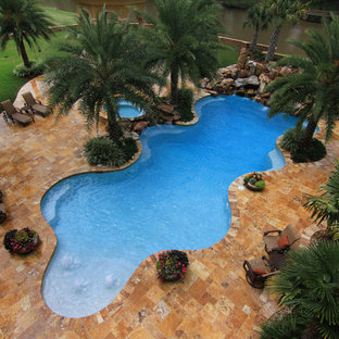 Tropical backyard custom-shaped pool in New Orleans with a water feature.