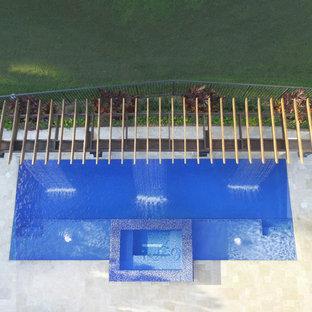 Hot tub - large modern backyard stone and rectangular hot tub idea in Miami