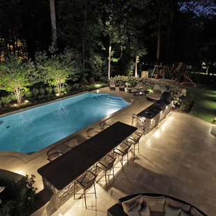 Inspiration for an expansive transitional backyard custom-shaped pool in New York with tile.