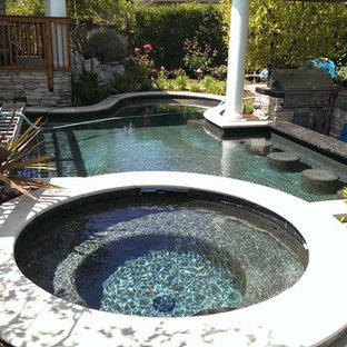 Diseño de piscinas y jacuzzis contemporáneos, de tamaño medio, redondeados, en patio trasero, con suelo de baldosas