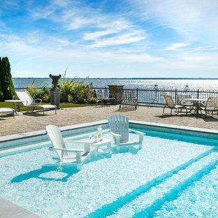 Ispirazione per una piscina design rettangolare di medie dimensioni e dietro casa con una dépendance a bordo piscina e pavimentazioni in mattoni