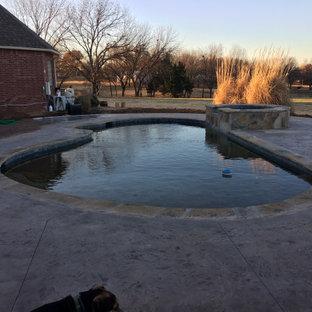 Diseño de piscina natural, de estilo americano, de tamaño medio, a medida, en patio trasero, con suelo de hormigón estampado