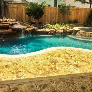 Foto di una grande piscina moderna personalizzata dietro casa con fontane e cemento stampato