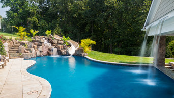 Custom pool with rock waterfalls, water slide & swim up pool bar.