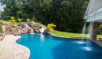 Custom pool with rock waterfalls, water slide & swim up pool bar.