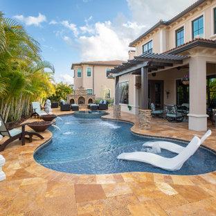 Mittelgroßer Mediterraner Pool hinter dem Haus in individueller Form mit Wasserspiel und Natursteinplatten in Miami