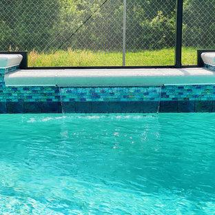 Aménagement d'une piscine arrière de taille moyenne et rectangle avec un aménagement paysager autour d'une piscine et des pavés en béton.