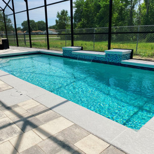 Imagen de piscina minimalista, de tamaño medio, rectangular, en patio trasero, con adoquines de ladrillo