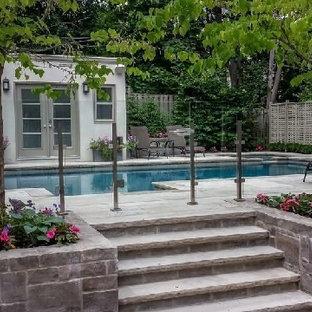 Modelo de casa de la piscina y piscina retro, de tamaño medio, rectangular, en patio trasero, con adoquines de piedra natural
