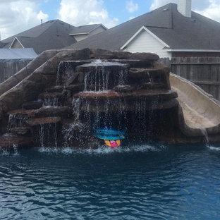 Esempio di una piscina naturale stile americano personalizzata di medie dimensioni e dietro casa con un acquascivolo