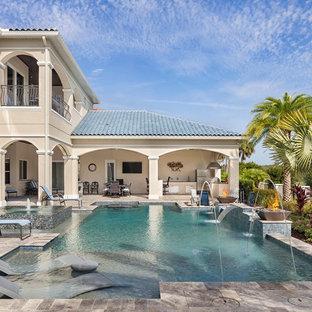 Пример оригинального дизайна: огромный прямоугольный бассейн на заднем дворе в средиземноморском стиле с фонтаном