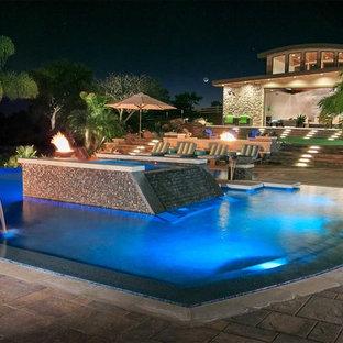 Foto de piscina con fuente infinita, exótica, grande, a medida, en patio trasero, con granito descompuesto