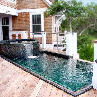 Diseño de piscina infinita, de estilo americano, a medida, en patio trasero, con entablado