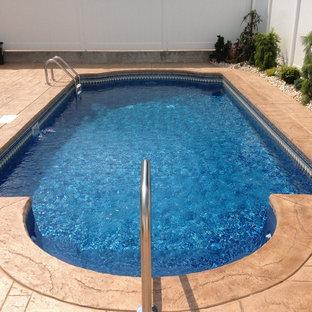 Modelo de piscina tradicional, de tamaño medio, a medida, en patio trasero, con adoquines de hormigón