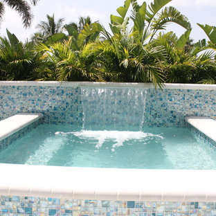 Inspiration for a small modern backyard concrete paver and rectangular aboveground hot tub remodel in Miami