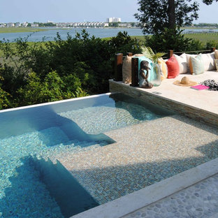 Example of a large trendy backyard tile infinity hot tub design in Wilmington