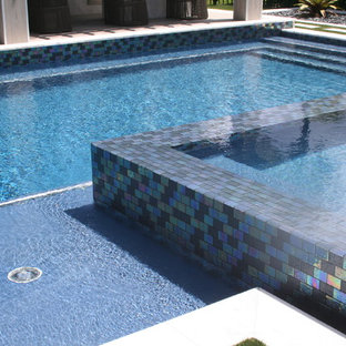 Example of a large minimalist backyard concrete paver and custom-shaped lap hot tub design in Miami
