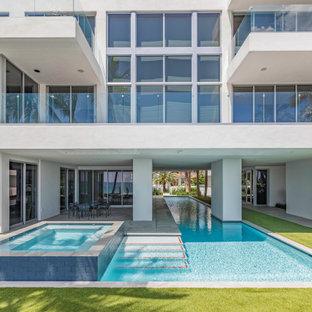 Ispirazione per una grande piscina monocorsia contemporanea personalizzata dietro casa con una vasca idromassaggio e pavimentazioni in cemento