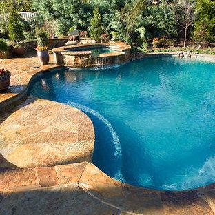 Immagine di una piscina naturale stile americano personalizzata di medie dimensioni e dietro casa con pavimentazioni in pietra naturale