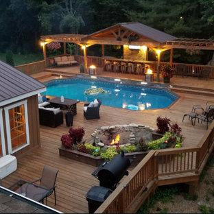 Foto de piscina elevada, de estilo americano, grande, a medida, en patio trasero, con entablado