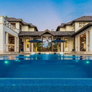 マイアミの長方形トロピカルスタイルのおしゃれなプール (噴水、タイル敷き) の写真