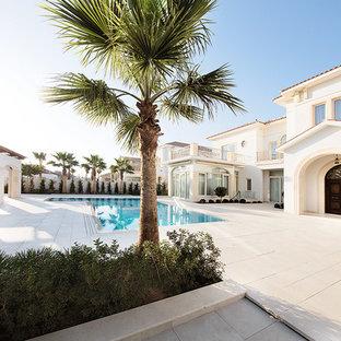 Großes Mediterranes Pool im Innehof in individueller Form mit Natursteinplatten in Sonstige