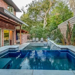 Imagen de piscinas y jacuzzis infinitos, clásicos renovados, de tamaño medio, rectangulares, en patio trasero, con losas de hormigón