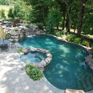 Diseño de piscina natural, actual, grande, a medida, en patio trasero, con adoquines de hormigón