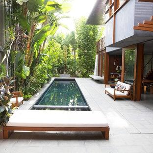 Esempio di una piscina monocorsia tropicale rettangolare in cortile