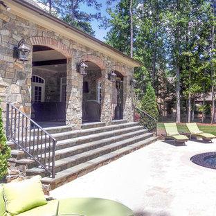 Immagine di una grande piscina boho chic personalizzata dietro casa con pavimentazioni in pietra naturale e una vasca idromassaggio