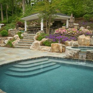 Cette photo montre une grand piscine arrière chic ronde avec des pavés en pierre naturelle et un bain bouillonnant.