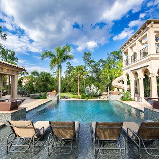 Идея дизайна: огромный прямоугольный бассейн-инфинити на внутреннем дворе в средиземноморском стиле с фонтаном и покрытием из плитки