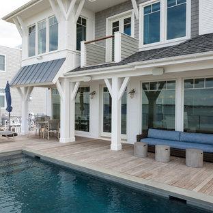 Immagine di una piccola piscina fuori terra stile marinaro rettangolare dietro casa con una vasca idromassaggio e pedane
