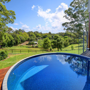 Mid-sized country backyard round aboveground pool in Perth with tile.