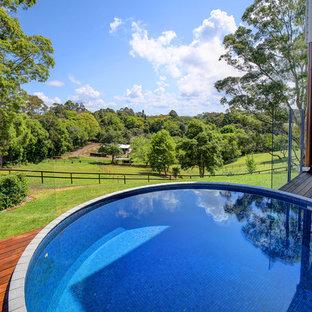 Modelo de piscina elevada, campestre, de tamaño medio, redondeada, en patio trasero, con suelo de baldosas