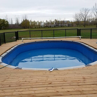 Example of a mid-sized arts and crafts backyard rectangular pool design in Other with decking