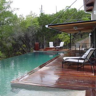 Foto de piscina infinita, actual, de tamaño medio, en forma de L, en patio trasero, con entablado